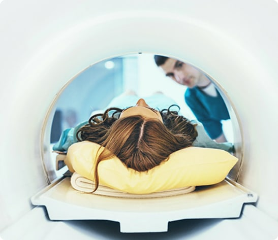 Man sitting on MRI machine smiling